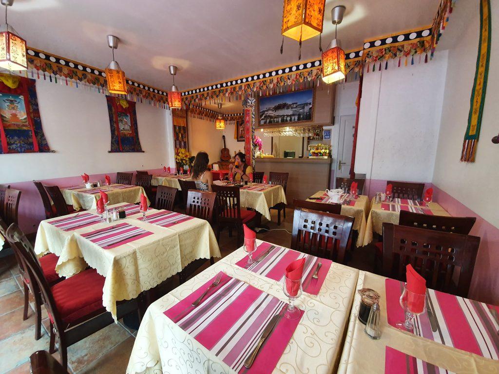 L'ambiance de son restaurant nous invite déjà au voyage : des fanions tibétains sont suspendus dans la pièce, des portraits du Dalaï Lama sont fixés au mur et semblent nous regarder.